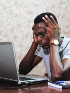 A frustrated man using a laptop, with his hands around his head.