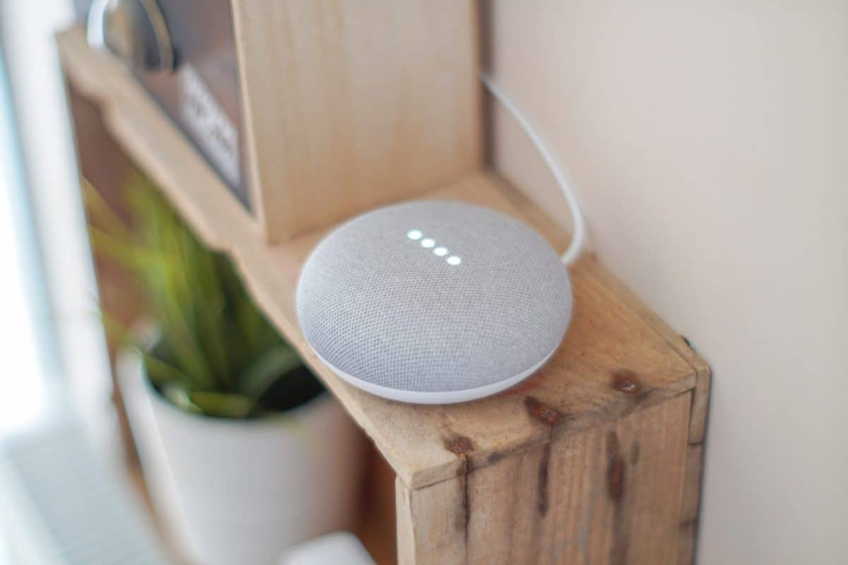A Google Home Mini device placed on a wooden shelving unit