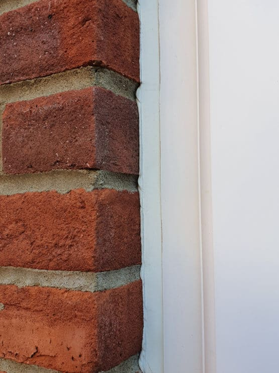 A very close up view of a thin UPVC door frame panel, with a brick wall to the left which would block lots of a wide-angle lens video capture.