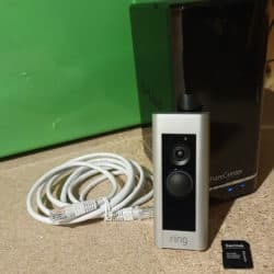 A Ring Doorbell Pro in-front of a D-Link ShareCenter NAS, and an SD-card adapter and Ethernet cable on the sides.