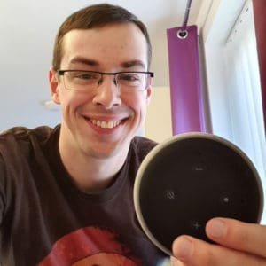 Picture of me holding up an Echo Dot in my house.