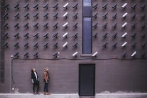 Two people standing under lots of bullet CCTV cameras