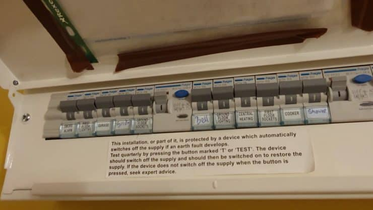 A metal consumer unit showing the labelled parts, including the 'Bell' and 'Ground Floor Lighting' switches.