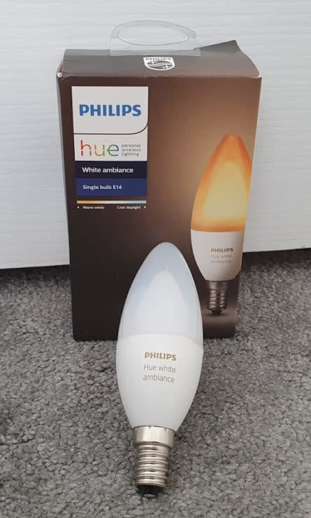 A Philips Hue White Ambiance E14 single bulb box, with the actual bulb outside it (resting against the box).