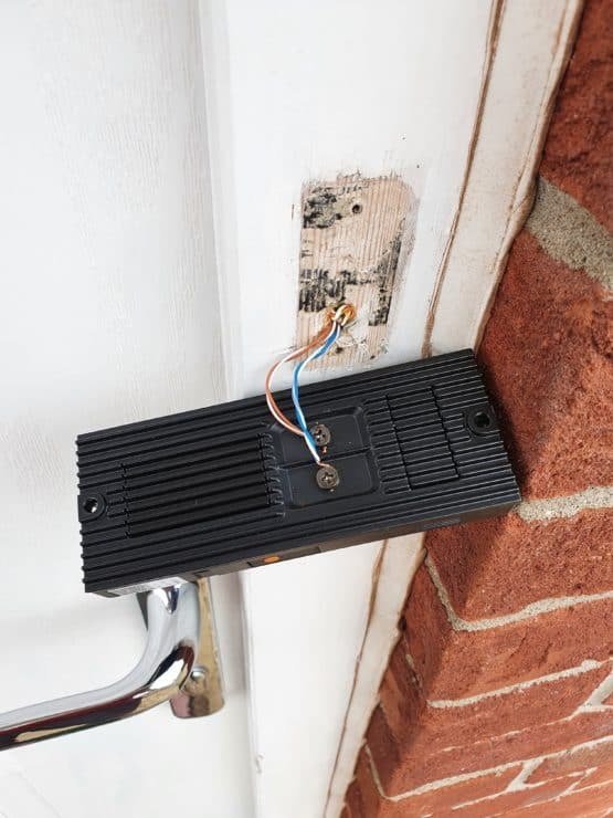 A Ring Doorbell Pro suspended in mid-air by the wired-up supply cables.
