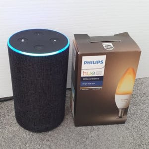 My Amazon Echo (with a blue ring, in listening mode) next to a Philips Hue E14 White Ambiance box.