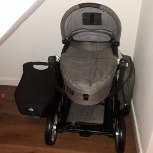 A pram and car baby seat, stored under our stairs in the hallway.