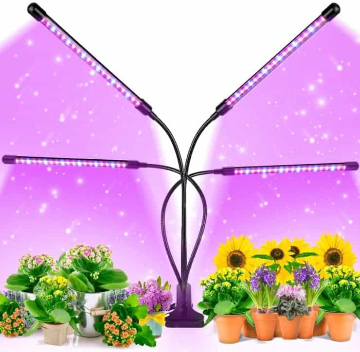 Marketing image for the EZORKAS multi-head LED grow light, showing it perched over multiple plants giving off a purple-ish light.
