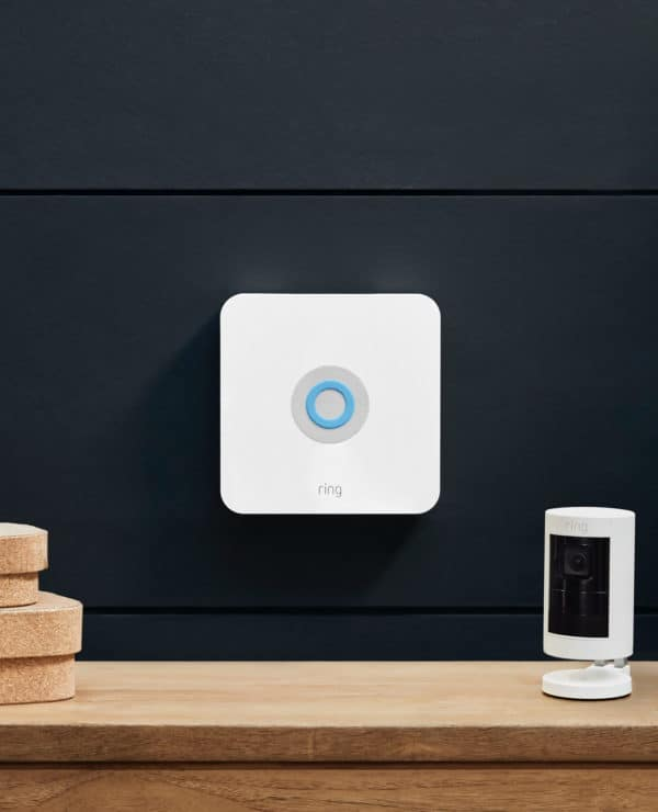 The Ring Alarm base station mounted on a wall above a shelf, with a Ring stick-up cam sitting on the shelf.
