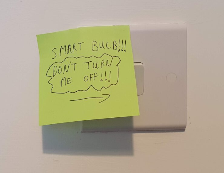 "A sticky note put over a standard wall switch, saying ""Smart bulb!!! Don't turn me off!!!"""