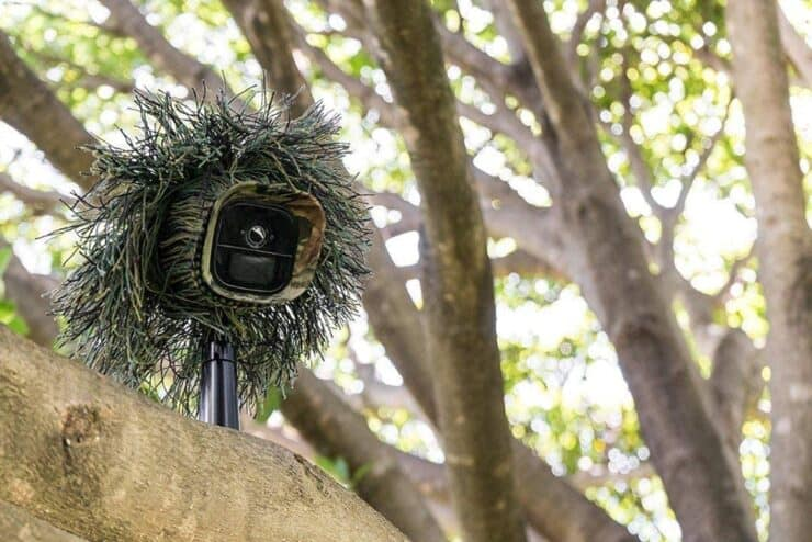 Marketing image of the Arlo Go mounted outside with camouflage.